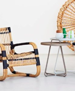 Unusual lounge chair, and a sure eye catcher, shaped from sustainable natural rattan with black bindings – lightweight yet strong and with a unique sculptural look.